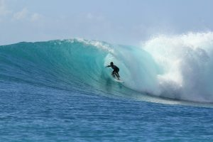 surfer cabalgando la ola con seguro multiaventura